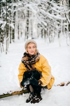 Bella ragazza bionda che siiting sull'albero in foresta nevosa.