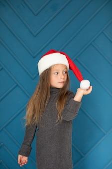 Bella ragazza bionda con cappello di babbo natale