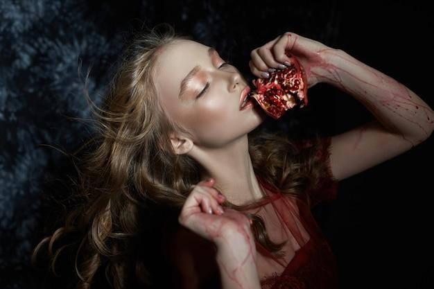 Bella ragazza bionda con frutta melograno nelle sue mani.