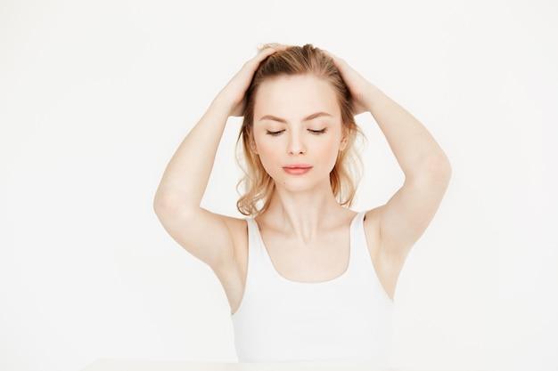 Bella ragazza bionda con pelle fresca pulita che si siede al tavolo toccando i capelli. bellezza e spa per la cura della pelle. occhi chiusi.
