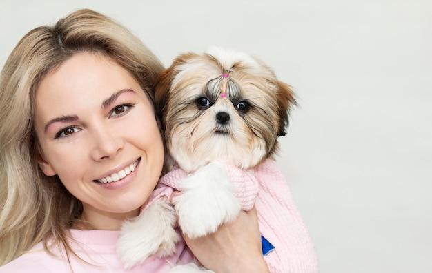 Bella ragazza bionda con un cucciolo carino shih tzu in abiti rosa su sfondo chiaro