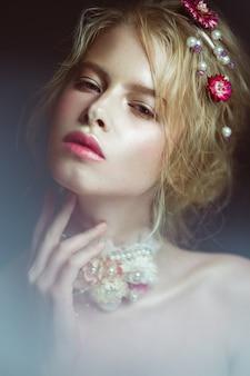 Bella ragazza bionda di moda con fiori sul collo e tra i capelli, trucco nudo bagnato