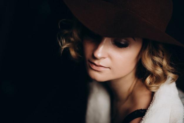 Bella ragazza bionda elegante in un cappello su un'oscurità