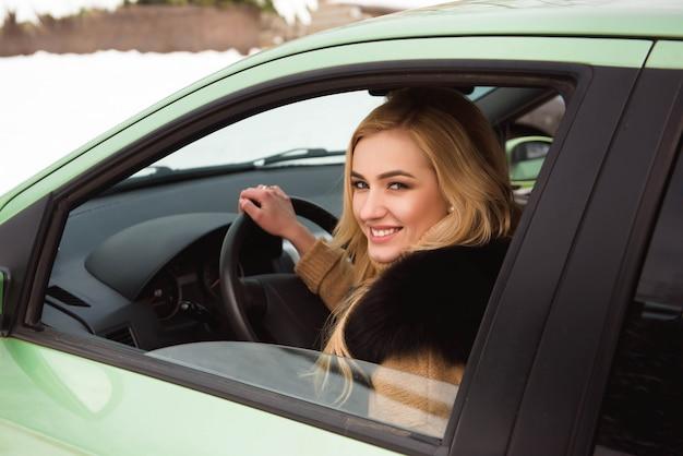 Bella ragazza bionda felice sul finestrino della macchina