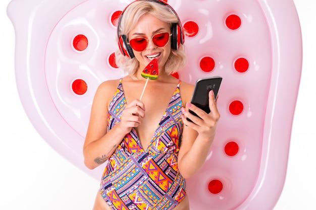 Bella ragazza bionda in costume da bagno e occhiali da sole con una lecca-lecca e un telefono in mano su un materasso da nuoto ascolta musica in cuffia