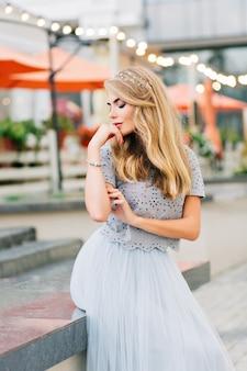 Bella ragazza bionda in gonna di tulle blu che si siede sul fondo della terrazza. sogna ad occhi chiusi.