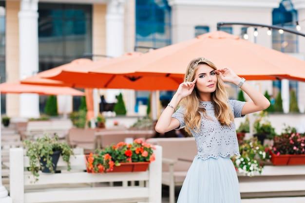 Bella ragazza bionda in gonna di tulle blu sta camminando sul fondo della terrazza.