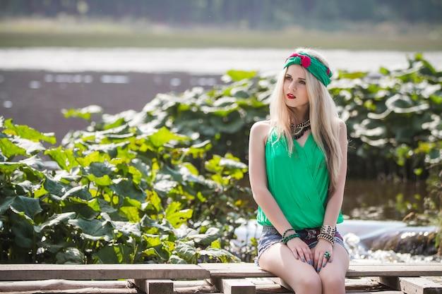 Bella ragazza bionda in pantaloncini e una fascia in un parco
