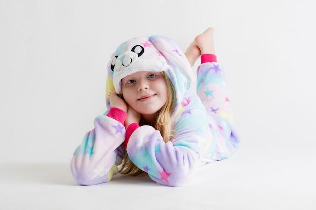 Bella ragazza bionda in posa su bianco in pigiama kigurumi, costume da coniglio