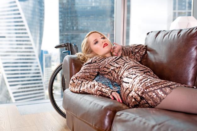 Bella ragazza bionda in un vestito alla moda con disabilità, in posa su un divano in pelle contro la vista di una finestra panoramica con vista sui grattacieli