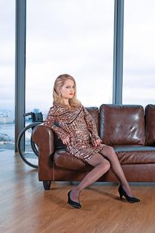 Bella ragazza bionda in un vestito alla moda con disabilità, in posa su un divano in pelle sullo sfondo di una finestra panoramica con vista sui grattacieli