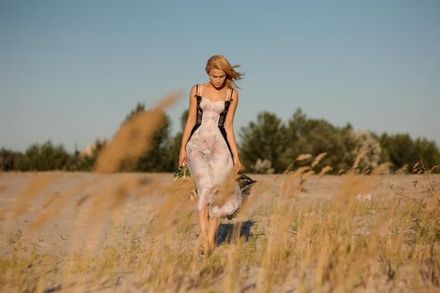 Bella ragazza bionda in una lingerie sul campo