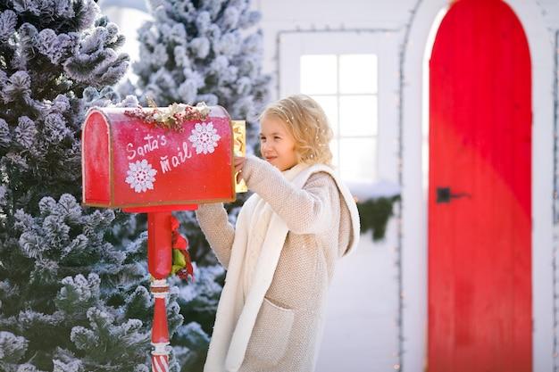Bella ragazza bionda riccia con la lettera vicino alla cassetta postale di babbo natale