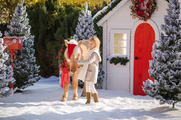 Bella ragazza bionda riccia e pony adorabile con ghirlanda festiva vicino alla piccola casa