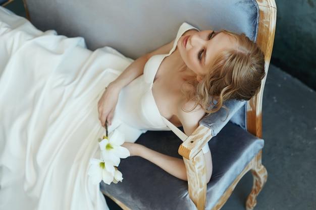 Bella ragazza bionda snella che si siede sul sofà in un vestito bianco lungo.