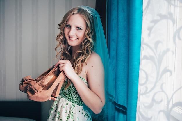 Bella ragazza bionda sorridente che tiene le scarpe da sposa nelle sue mani