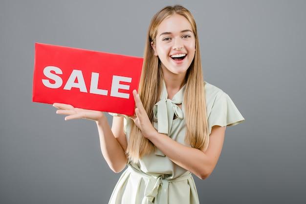 Bella ragazza bionda sorridente con il segno di vendita isolato