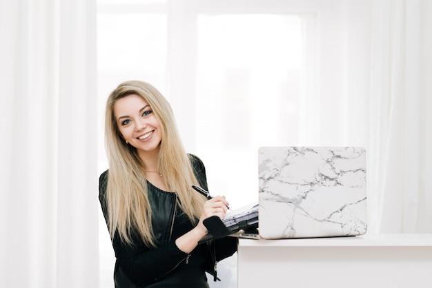 Bella ragazza bionda sorridente con un taccuino e una penna in mano, accanto a un computer portatile su una finestra leggera, impiegato
