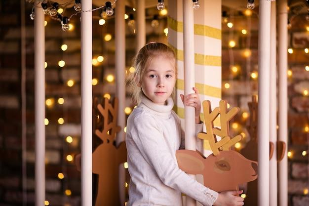 Bella ragazza bionda sulla giostra di capodanno con cervi in legno e luci intense