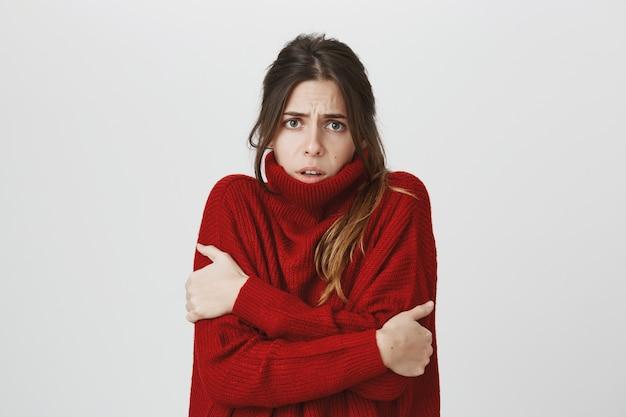 Bella ragazza carina sensazione di freddo, abbracciando se stessa, indossa maglione
