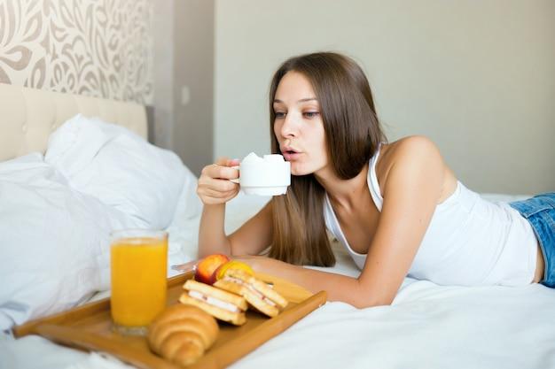 Bella ragazza castana che mangia prima colazione e che beve caffè a letto