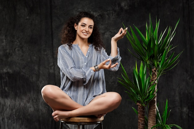 Bella ragazza castana che medita in piante tropicali sopra la parete grigia
