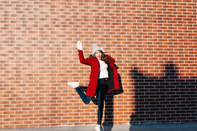Bella ragazza castana con capelli lunghi che hanno divertimento sul muro esterno. indossa cappotto rosso, guanti bianchi e cappello lavorato a maglia.