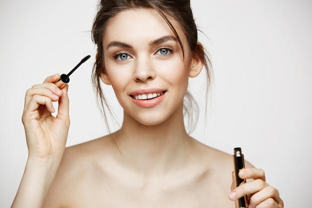 Bella ragazza castana con pelle pulita perfetta che sorride esaminando mascara della tenuta della macchina fotografica sopra fondo bianco. trattamento facciale.