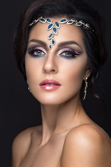 Bella ragazza castana con trucco arabo di sera e pelle perfetta