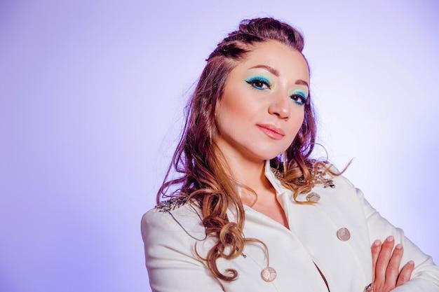 Bella ragazza castana con trucco nei toni del blu, trecce e in una giacca bianca in posa su uno sfondo di viola. foto orizzontale