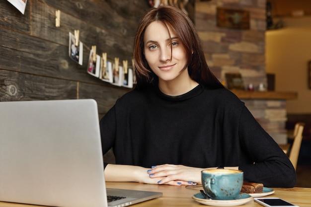 Bella ragazza castana con un sorriso affascinante che si siede al caffè da solo