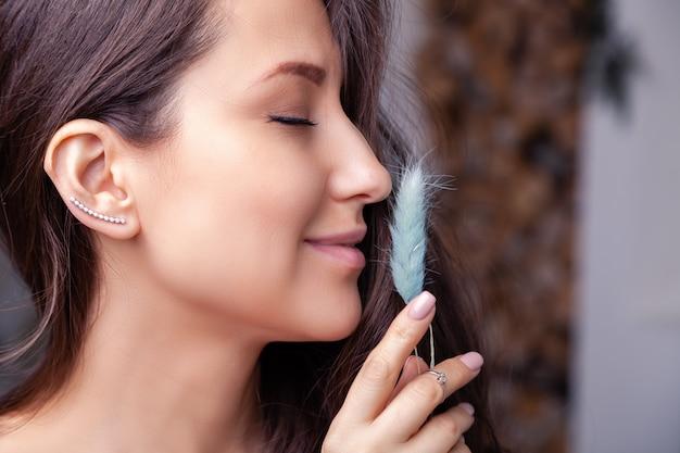 Bella ragazza castana del primo piano con capelli lunghi in orecchini, anelli, braccialetto, catena, collana dei gioielli d'argento moderni.