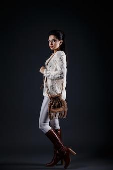 Bella ragazza castana in maglione beige e borsa marrone