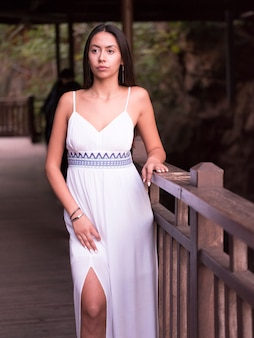 Bella ragazza castana in un vestito bianco che distoglie lo sguardo la natura