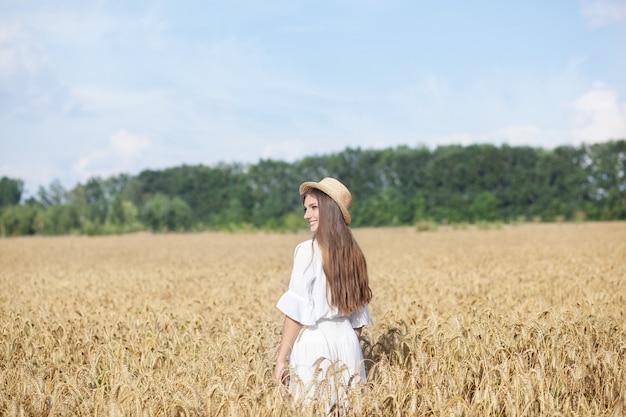 Bella ragazza castana in vestito bianco ed in cappello di paglia che stanno nel campo di frumento al tramonto. raccolta