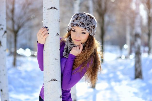 Bella ragazza castana su una passeggiata in inverno vicino alla betulla