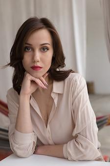 Bella ragazza caucasica con labbra rosse in elegante camicetta beige guarda pensieroso nella fotocamera, appoggiandosi sul tavolo di caffè
