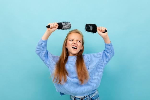 Bella ragazza caucasica dell'adolescente con capelli marroni in maglia con cappuccio blu con i pettini dei capelli isolati sul blu