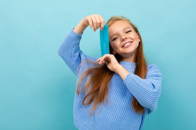 Bella ragazza caucasica dell'adolescente con capelli marroni in maglia con cappuccio blu con il pettine blu isolato su fondo blu