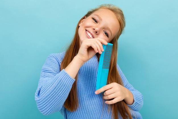 Bella ragazza caucasica dell'adolescente con capelli marroni in maglia con cappuccio blu con il pettine blu isolato sul blu
