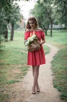 Bella ragazza caucasica in abito rosso in possesso di un sacchetto di cibo