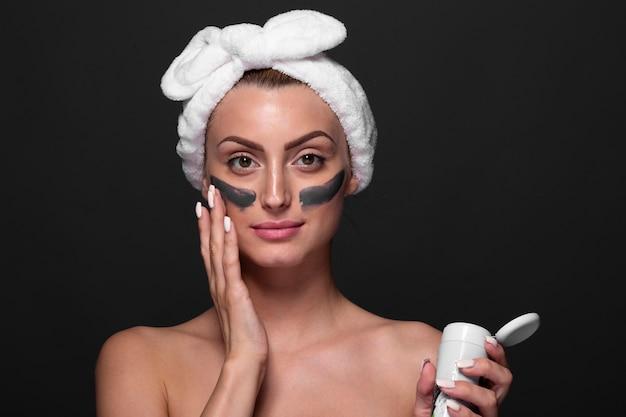Bella ragazza che applica i prodotti per la cura della pelle