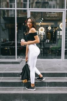 Bella ragazza che beve caffè in città