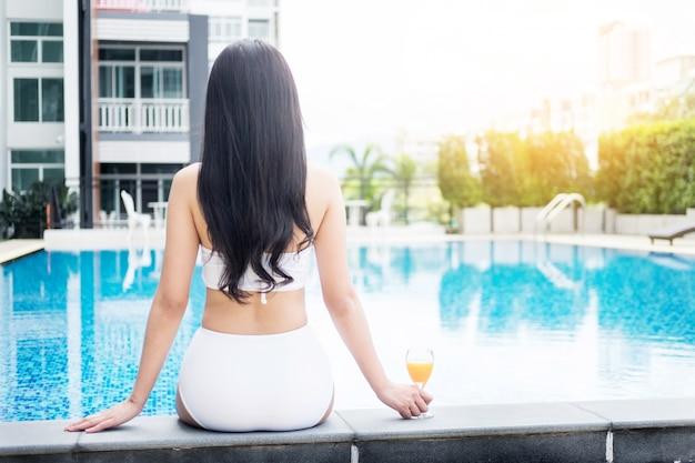 Bella ragazza che beve cocktail cosmopolita, piscina di menzogne, concep di vacanze estive