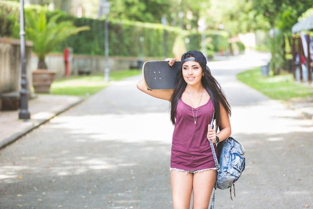 Bella ragazza che cammina al parco tenendo uno skateboard.