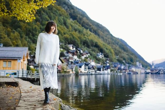 Bella ragazza che cammina intorno al lago di autunno