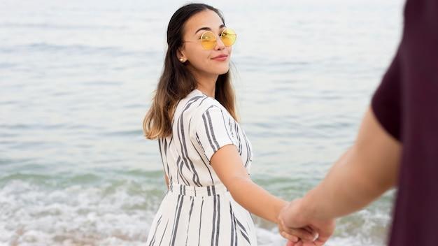 Bella ragazza che cammina lungo la spiaggia