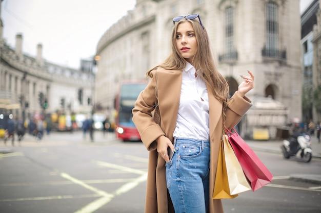 Bella ragazza che cammina per strada, portando borse della spesa