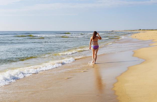 Bella ragazza che cammina sulla spiaggia estiva