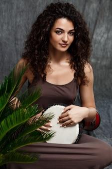 Bella ragazza che gioca tamburo in piante tropicali sopra la parete grigia